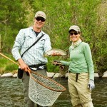 fishing guide and guest proudly hold up caught trout before releasing