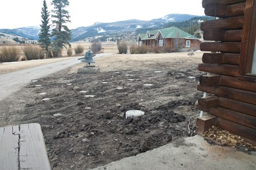 view from lodge porch of area where new deck will be. Concrete footers are buried in uncovered earth