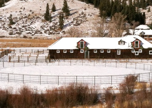 round arena on east side of historic barn with fresh snow on ground