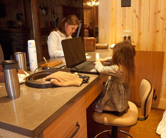 little girl plays receptionist on laptop computer in new reception area