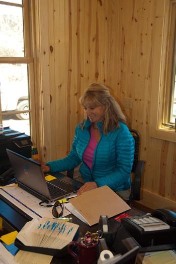 blonde woman with blue jacket smiles at computer at colorado fly fishing guest ranch