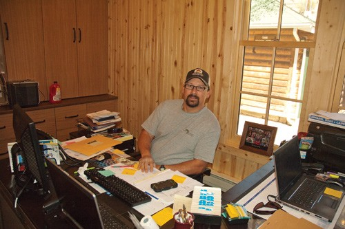 man with glasses sits behind work desk at colorado guest ranch lodge