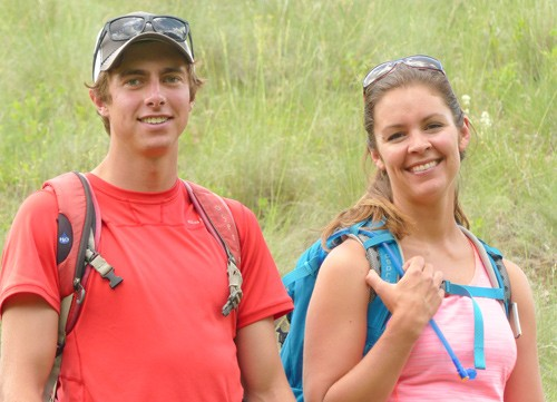 male and female hiking guides stand with backpacks in front of a flowery hillside