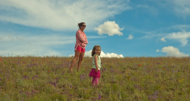 mother and daughter stand on flower covered mountainside with bright blue sky in background