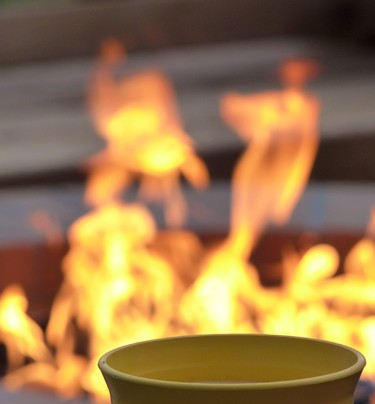 close up of top of a citronella candle with fire pit burning in background