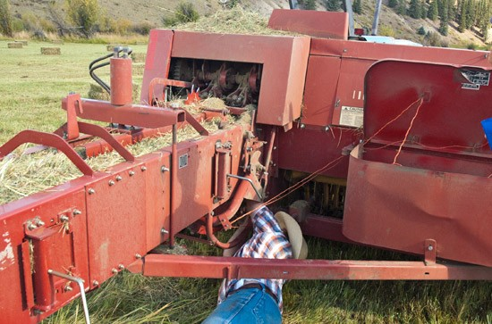 ranch hand works under hay baler to correct feeding of twine