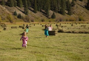 four little girls run toward camera among colorado sunlit hay bales with rocky mountain pines in the distance