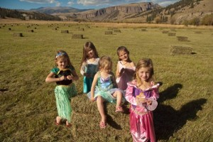 five little girls stand in foreground among hay bales and colorado san juan mountains in the background