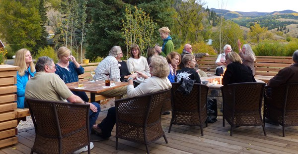 group sit on open deck with wine and blazing fire pit