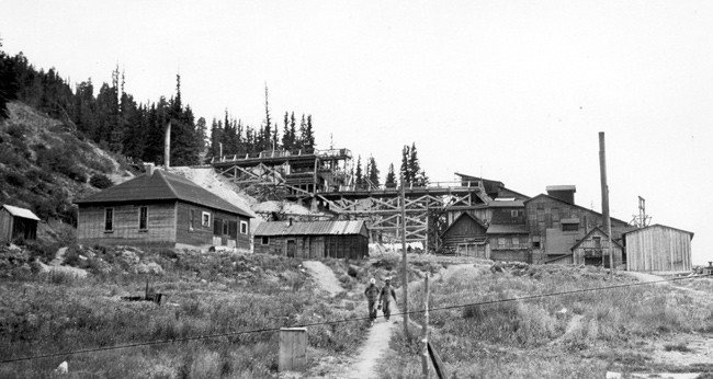 historic photo of two miners walking down hill from fluorspar mill