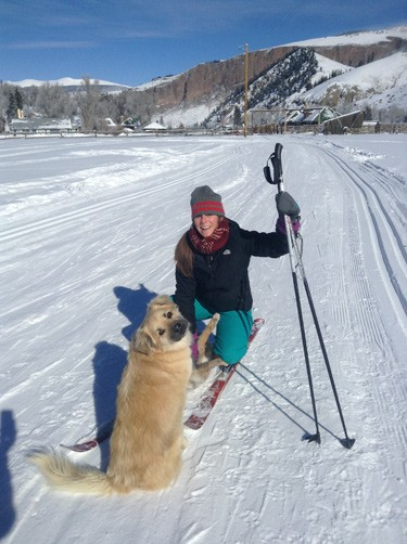 woman squats to pet dog during her ski. Both look toward camera