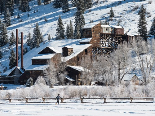 lone skier on groomed path in front of old fluorspar mill