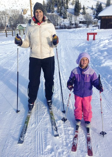 woman and girl smile for camera with cross-country skis strapped on