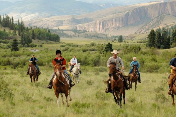 group of ranch guests on a running ride toward camera, in natural horsemanship program. Mountain pallisades and river in background.
