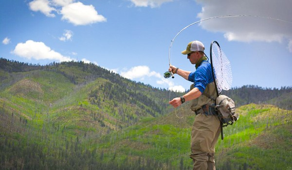 a sunny blue sky with green mountains in the background and a fly fishing guide in the foreground practicing his cast
