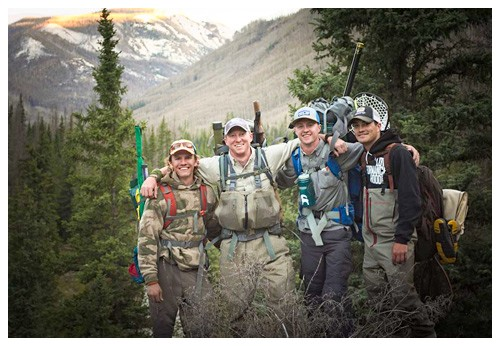 four fly fishing guides pose in the foreground of pine trees with Colorado Rocky Mountains in background