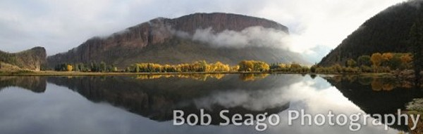 a fog hangs over pallisade cliffs with large pond in foreground separated by gold aspen trees