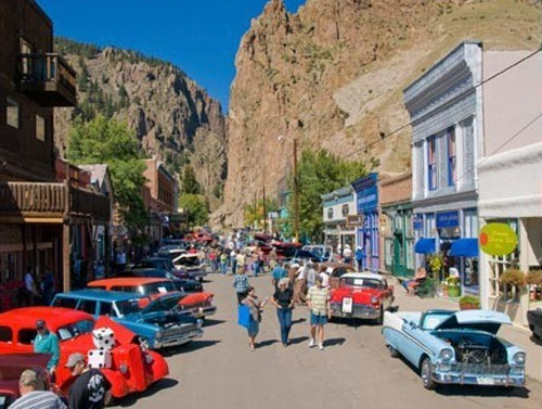 small arts town of creede with cliffs in background and car show vehicles and viewers in foreground