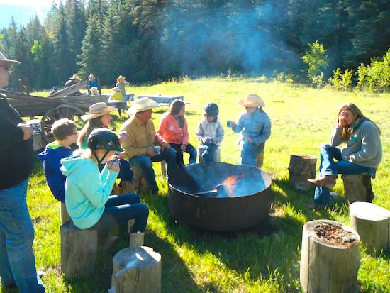 Families sitting around a firepit at the first morning sun