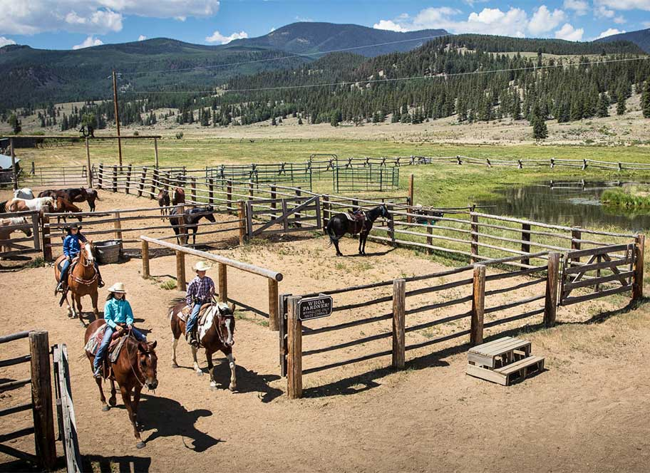 Horse riding group leaving penning area