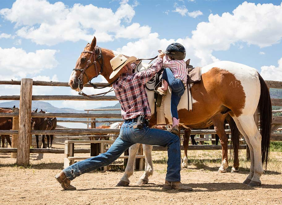 Instructor helping child mount horse