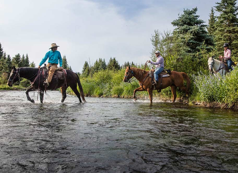 Horseback riders crossing river