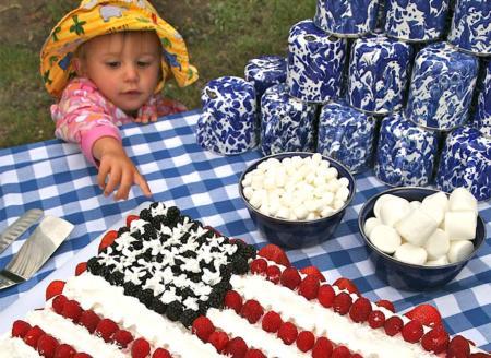 Toddler reaching for US flag cake
