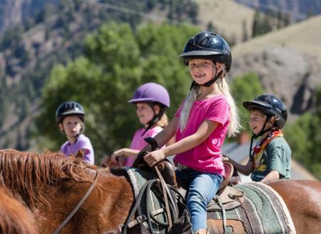 Girls in helmets riding horses