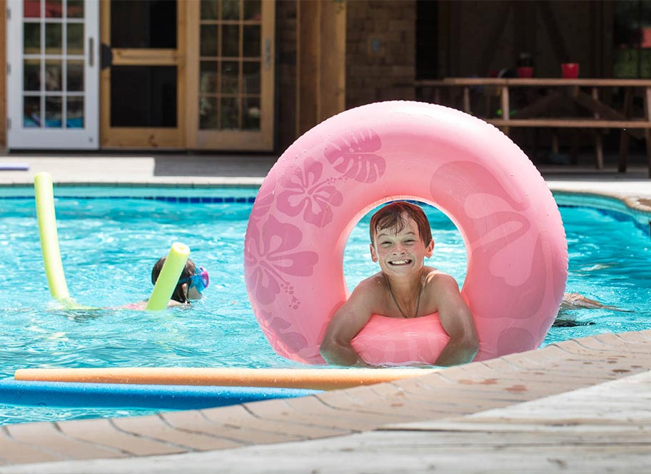 Smiling boy in pink inner tube